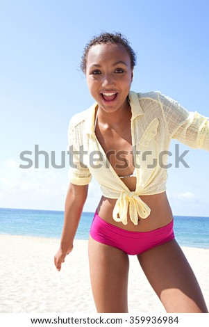 Beautiful adolescent african american teenager feeling fresh and carefree on a sunny beach destination against a blue summer sky, outdoors. Adolescent joyful wellness lifestyle, colorful exterior. - stock photo