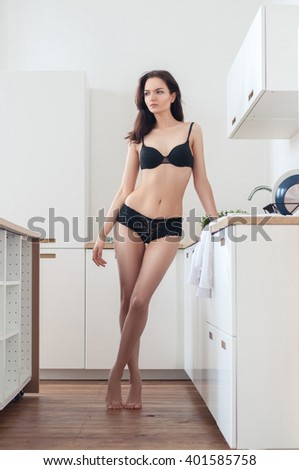 beautiful adorable cute slim female in underwear standing in kitchen