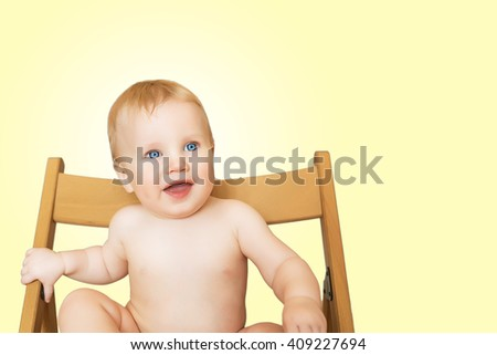 Beautiful adorable laughing baby boy infant face, isolated on light yellow background. Smiling blue-eyed child sits on a chair - stock photo