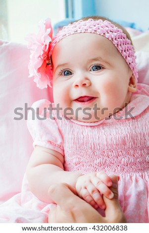 Beautiful adorable little girl in a pink dress with a bow, smiling. A happy childhood of the child. Background, closeup, macro - stock photo
