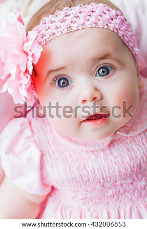 Beautiful adorable little girl in a pink dress with a bow, smiling. A happy childhood of the child. Closeup, macro.