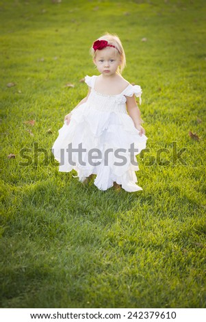 Beautiful Adorable Little Girl Wearing White Dress In A Grass Field. - stock photo