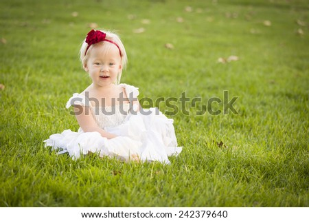 Beautiful Adorable Little Girl Wearing White Dress Sitting In A Grass Field. - stock photo