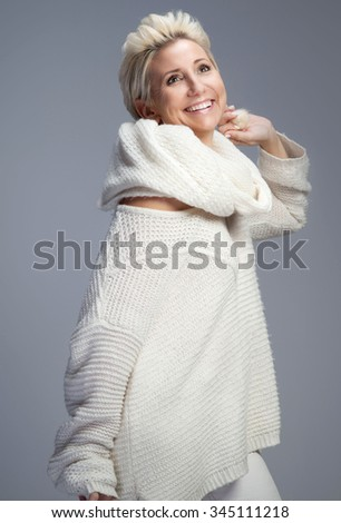 Beautiful adult blonde woman with short hair posing in studio, smiling. Lady wearing sweater and scarf. - stock photo