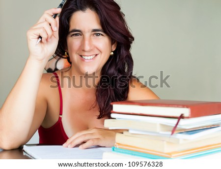 Beautiful adult hispanic woman studying  with a stack of books on her desk and smiling at the camera
