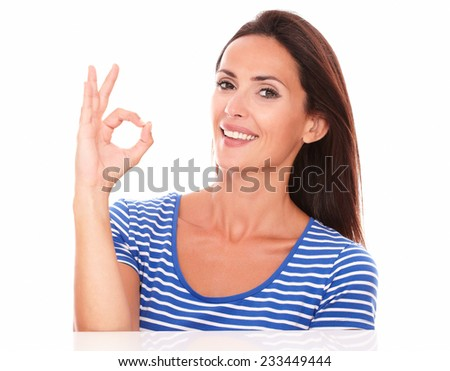 Beautiful adult lady gesturing a great job while looking at camera in white background - stock photo