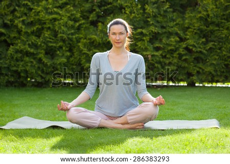 beautiful adult woman doing yoga on the grass in the park