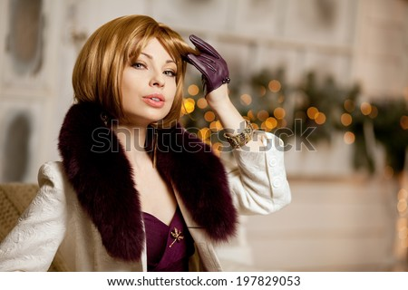 Beautiful adult woman in a winter coat with fur. Trendy modern blondy girl with short hair