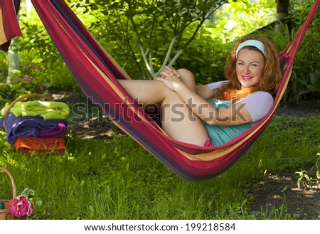 beautiful adult woman resting bright multicolored hammock in garden of country house