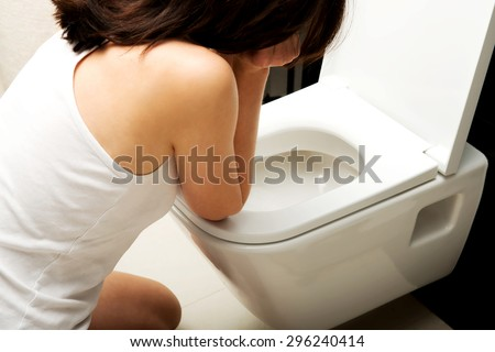 Beautiful adult woman vomiting in toilet. - stock photo
