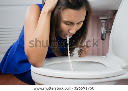 Beautiful adult woman vomiting in toilet - stock photo