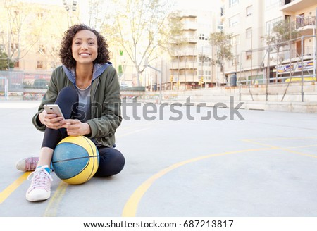 Beautiful african american college student in basketball court with basket ball and smart phone, outdoors joyful smiling. Black teenager using technology, sport activities lifestyle, networking.