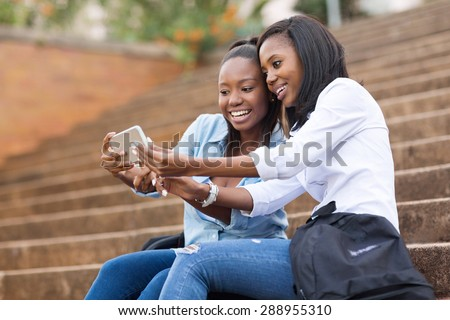 beautiful african american college students using cell phone on campus - stock photo
