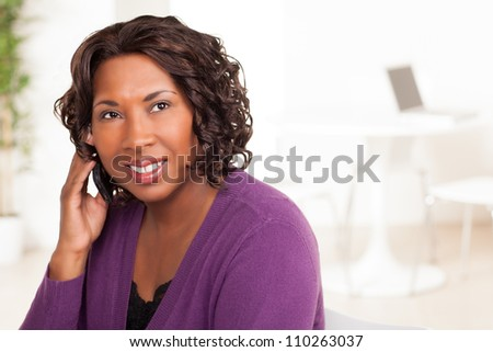 Beautiful African American female executive with dark brown hair at work in an office setting wearing a purple sweater.