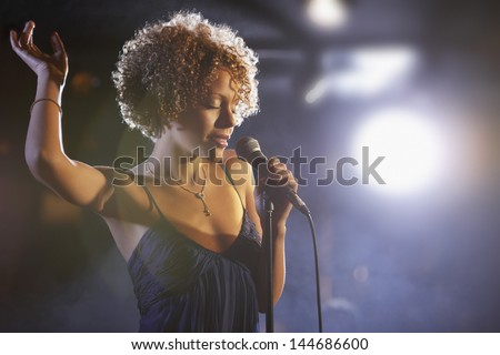 Beautiful African American female jazz singer on stage - stock photo
