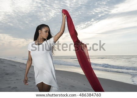 Beautiful African American female model posing on beach in white dress - holding red fabric in the breeze