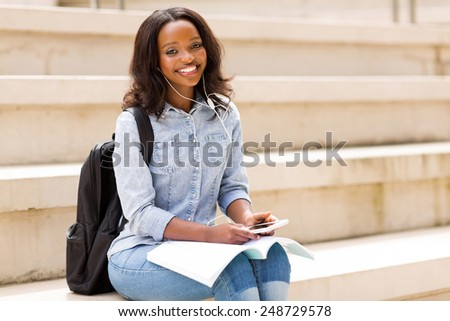 beautiful african american female student listening to music on campus - stock photo