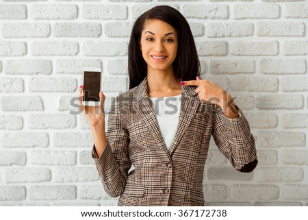 Beautiful African American girl hold the phone in hands on a gray background - stock photo