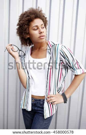 Beautiful African-American girl wearing striped shirt and glasses posing on a metal background. Unusual female model. Hipster student style outfits
