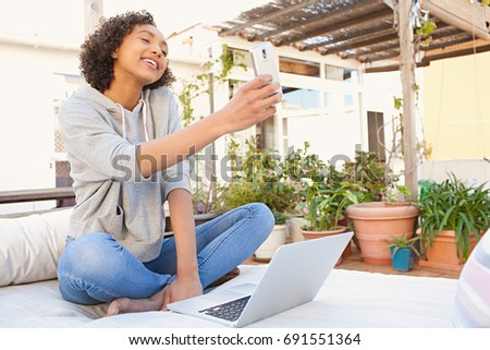 Beautiful african american teenager girl pointing smart phone photo camera taking selfies pictures, joyful smiling, home exterior. Black female using laptop computer social media, fun technology.