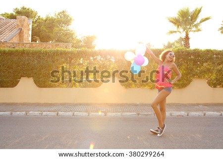 Beautiful african american teenager girl with joyful expression having fun in home exterior suburban street, holding balloons up in the air, laughing outdoors sunset. Fashionable adolescent lifestyle. - stock photo