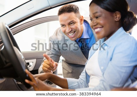 beautiful african american woman buying a car at dealership - stock photo