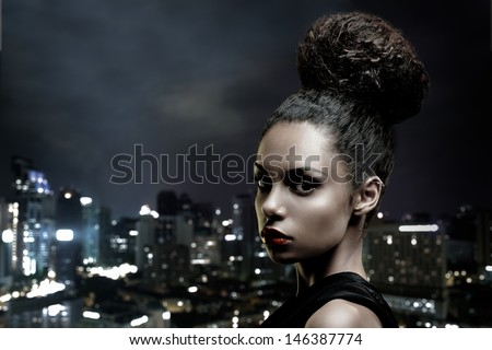 Beautiful African-American woman in front of a big city outline. - stock photo