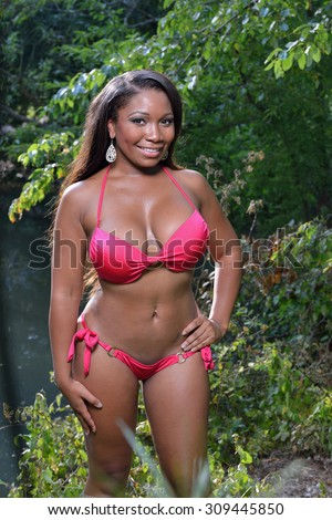 Beautiful African-American woman in red bikini stands in front of small pond - summer - stock photo