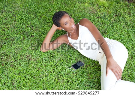 Beautiful african american woman laying on park green grass using smart phone and headphones, outdoors living. Black girl using technology, smiling in exterior. Color intense.