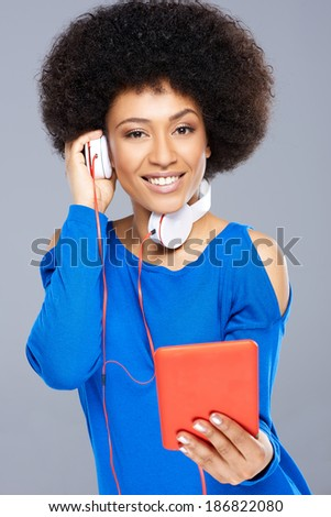 Beautiful African American woman listening to music downloaded on her tablet computer holding one of the earphones to her ear while smiling happily at the camera - stock photo