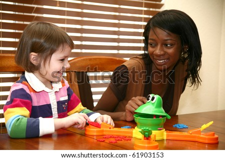 Beautiful african american woman playing games with 5 year old girl. - stock photo
