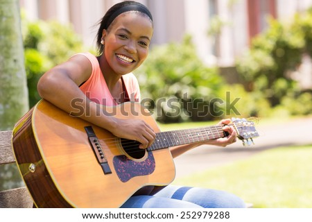 beautiful african american woman playing guitar outdoors - stock photo