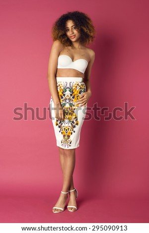 Beautiful African American woman posing in nice flower pattern skirt and white bra on a pink background. Fashion photo with afro hairstyle.