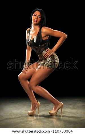Beautiful African American woman posing over dark background - stock photo
