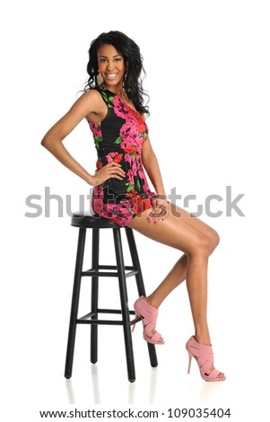 Beautiful African American woman sitting on stool isolated over white background - stock photo