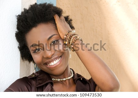Beautiful African American woman smiling outdoors - stock photo