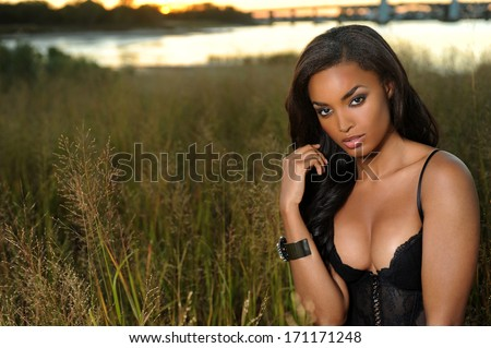 Beautiful african-american woman wearing black lingerie corset at the sunset at grass field - stock photo