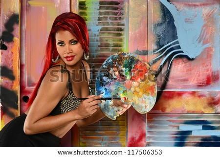 Beautiful African American woman with paintbrush and palette over colorful background