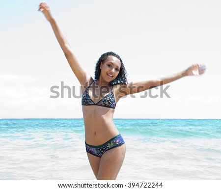 Beautiful african american young woman bathing playfully stretching her arms on a sunny summer holiday, joyful, coastal exterior. Travel lifestyle enjoying the sun on beach shore. Body figure. - stock photo