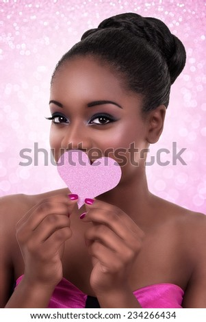 Beautiful African black woman wearing makeup and holding glitter heart for love or Valentine Day - stock photo