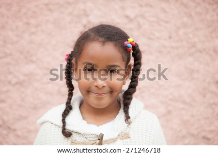 Beautiful african child with a brick a pink wall of background - stock photo