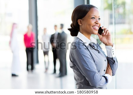 beautiful african corporate worker talking on mobile phone - stock photo