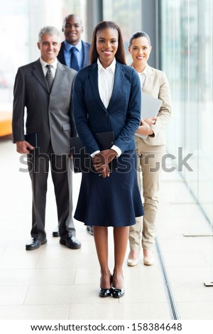 beautiful african female business leader with team standing on background - stock photo