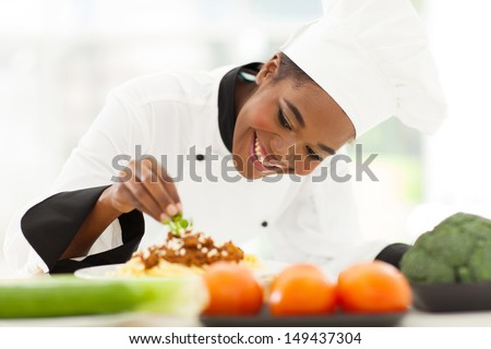 beautiful african female chef garnishing spaghetti dish - stock photo