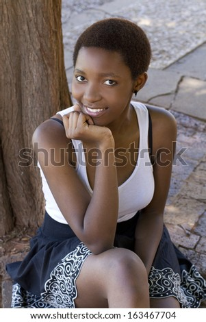 Beautiful African girl outside looking straight into the camera - stock photo