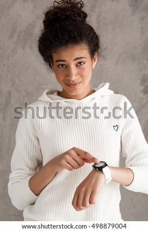 Beautiful african girl pointing finger at wristwatch over beige background.