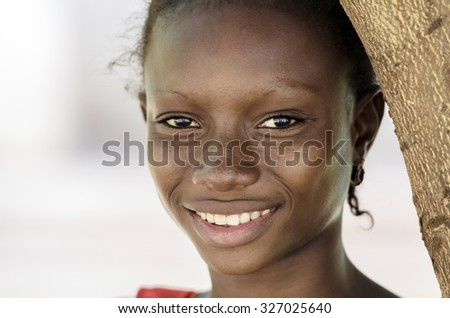 Beautiful African Teenage Woman Fashion Portrait Light Toothy Smile. Gorgeous beautiful African teenage girl posing in the streets of Bamako, Mali. Nice smile on her face, standing next to a tree. - stock photo