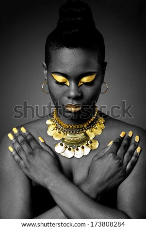 Beautiful African tribal fashion with gold eyeshadow and necklace on dark with arms crossed and looking down. - stock photo