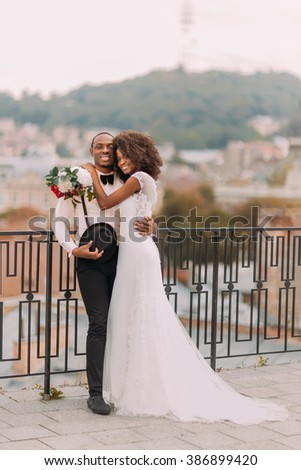 Beautiful african wedding couple standing on the balcony on their wedding day - stock photo