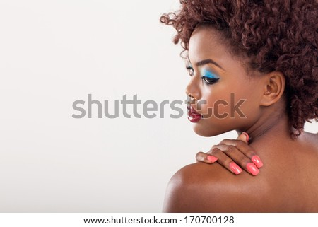 beautiful african woman looking over her shoulder on plain background